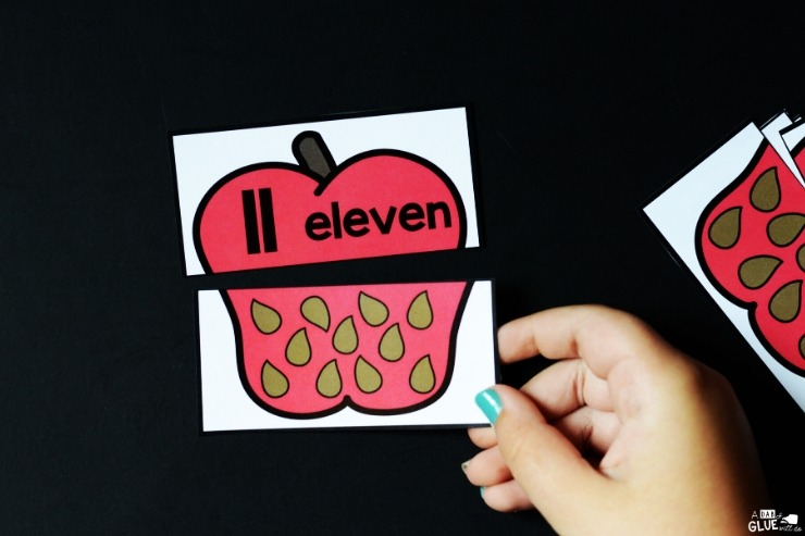 Hand placing apple seed card under matching number 11 apple top card.