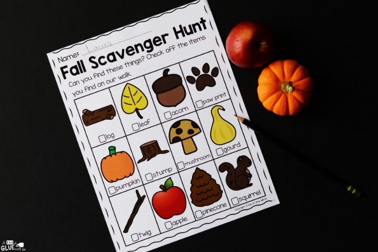 Overhead shot of the Fall Scavenger Hunt activity free printable on a black background with a small pumpkin and apple next to it.