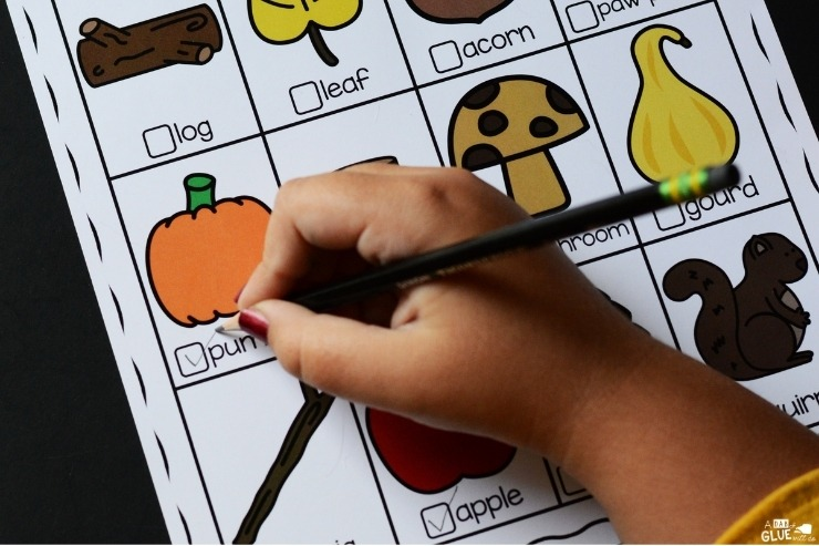 Close up of a child marking off the pumpkin on the scavenger hunt free worksheet.