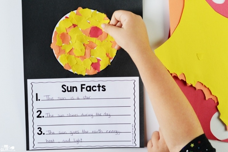 Overhead shot of a child using torn pieces of construction paper to complete a lesson sheet about Sun Facts.