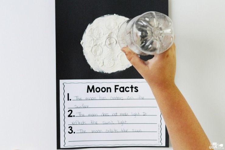 Overhead shot of a child creating a moon art project on a Moon Facts lesson sheet.