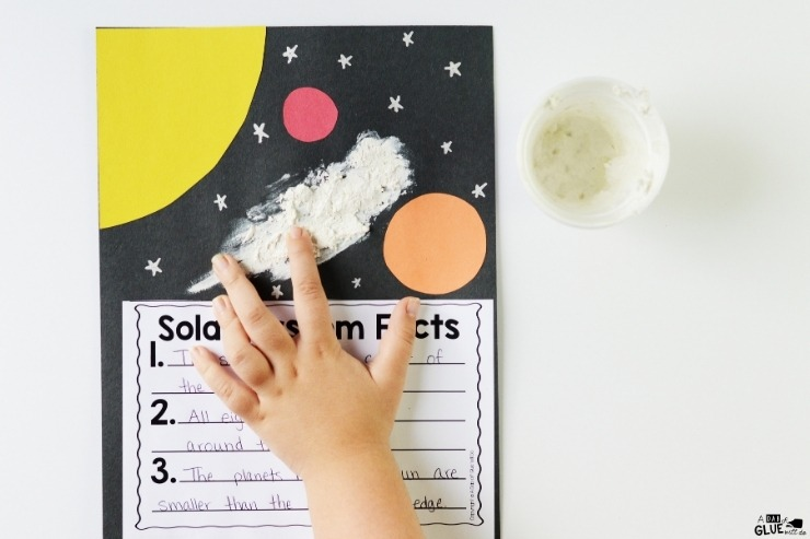 Overhead shot of a child completing a lesson sheet on Solar System Facts.