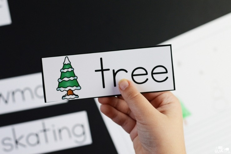 "Overhead view of a child's hand holding the ""tree"" Winter Writing Center writing prompt card."