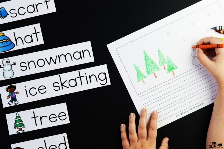Overhead view of a child illustrating the winter themed writing prompts for the winter writing center.