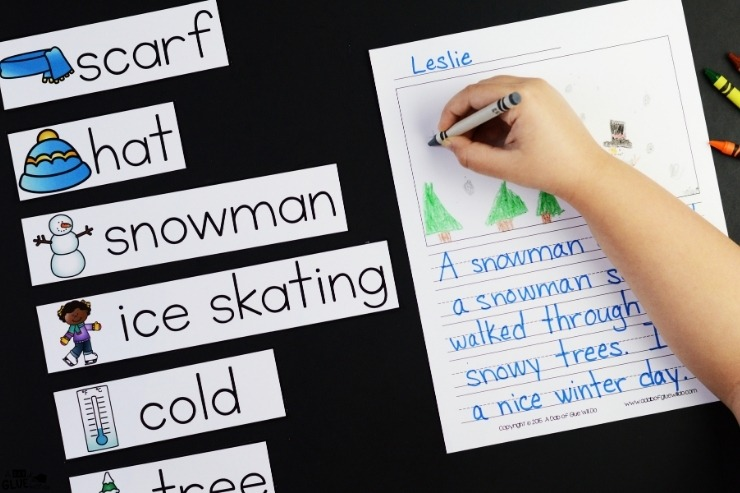 Overhead view of a child completing the winter writing activity with winter themed word prompt cards to the side.