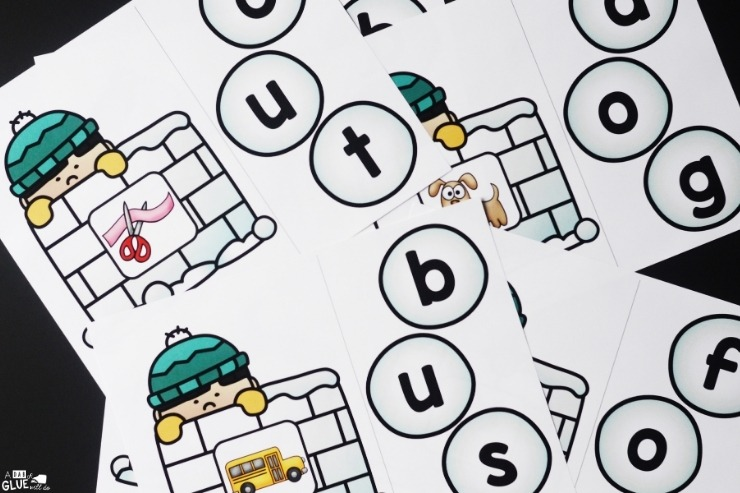 The Snowball CVC Word Building Freebie printed out and laid out on a black background.