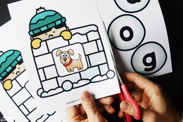 Closeup of a hand cutting out a puppy card for the Snowman CVC Word Building Freebie.