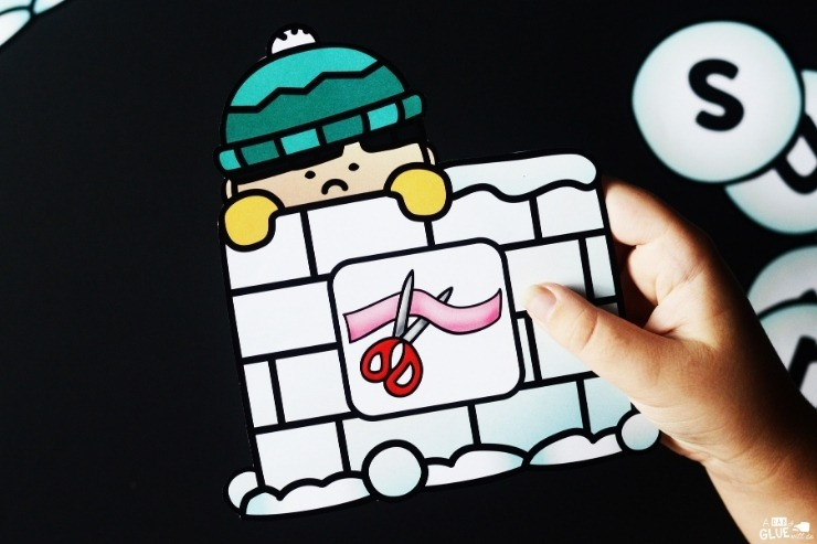 """A student holding a """"cut"""" matching card for the Snowman CVC Word Building Freebie."""