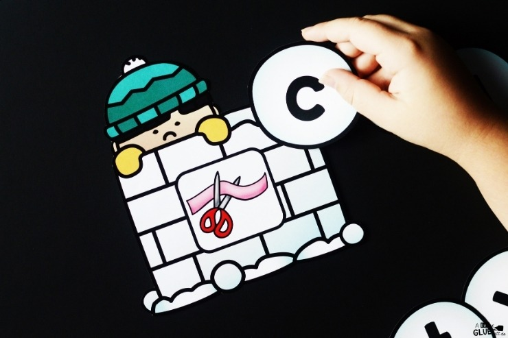 "A kid placing the letter ""c"" next to a ""cut"" card."