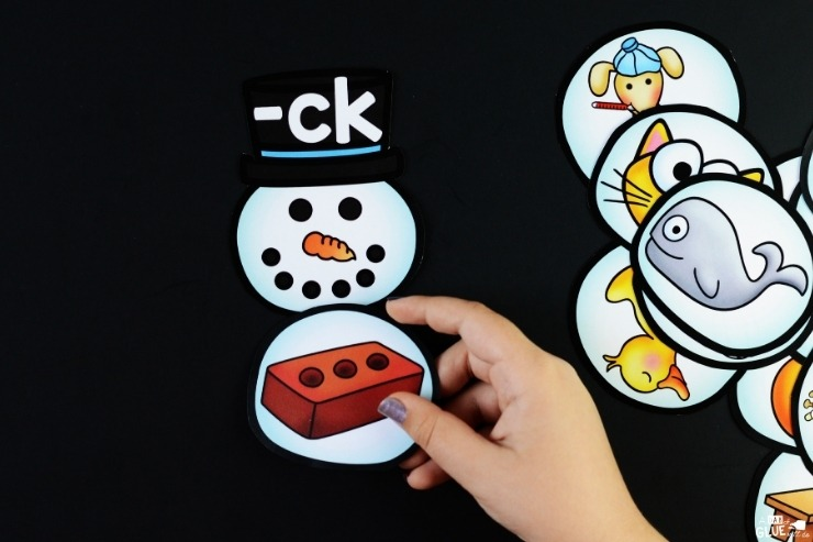 """A child's hand completing the snowman digraph for """"-ck""""."""